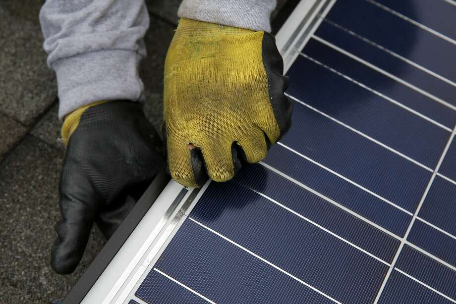 Jonathan Munoz installs a solar panel on the roof of a house in Los Gatos, California, on Tuesday, Aug. 4, 2015. Photo: Connor Radnovich, The Chronicle