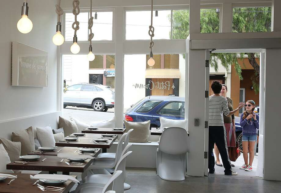 Chef/owner Dominique Crenn (striped shirt) talks to neighbors Shawn Halbert and nine year old Lily Halbert-Alexander (right) at Petit Crenn San Francisco, Calif., on Tuesday, August 4, 2015.  Petit Crenn is a neighborhood restaurant inspired by chef Dominique Crenn's mother, grandmother and her home in Brittany, France. Photo: Liz Hafalia, The Chronicle