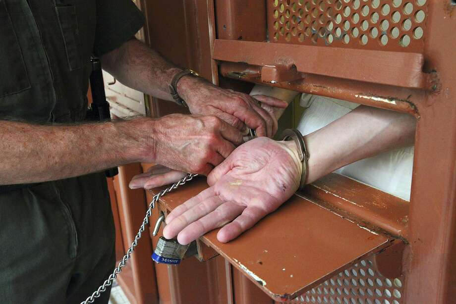 A guard puts handcuffs on an inmate before opening his cell door in the Secured Housing Unit, where prisoners are held in isolation in windowless cells, at Pelican Bay State Prison in Crescent City, Calif., Feb. 9, 2012. Photo: Jim Wilson, New York Times