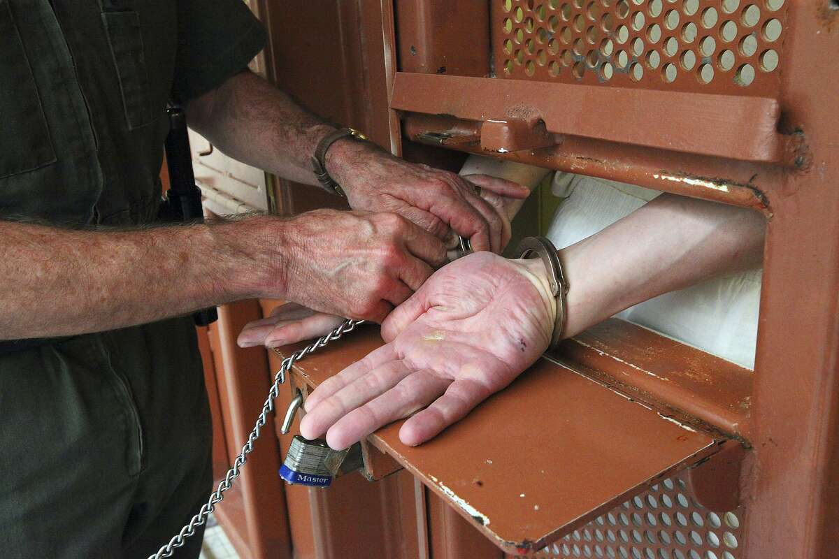 A guard puts handcuffs on an inmate before opening his cell door in the Secured Housing Unit, where prisoners are held in isolation in windowless cells, at Pelican Bay State Prison in Crescent City, Calif., Feb. 9, 2012.