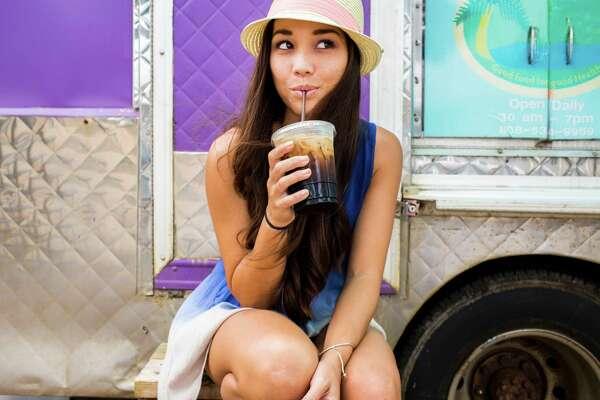 Woman drinking ice coffee near food cart