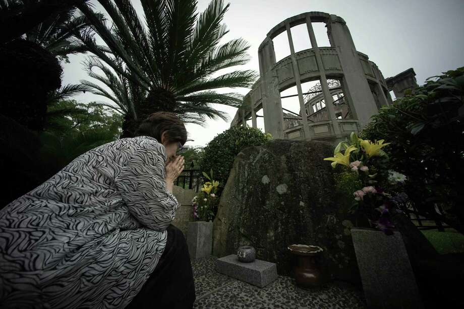Kimie Mihara, a survivor of the atomic bombing, prays at the cenotaph at the Atomic Bomb Dome in Hiroshima. Mihara was a worker at a government office in the dome building on Aug. 6, 1945. Photo: Eugene Hoshiko / Eugene Hoshiko / Associated Press / AP