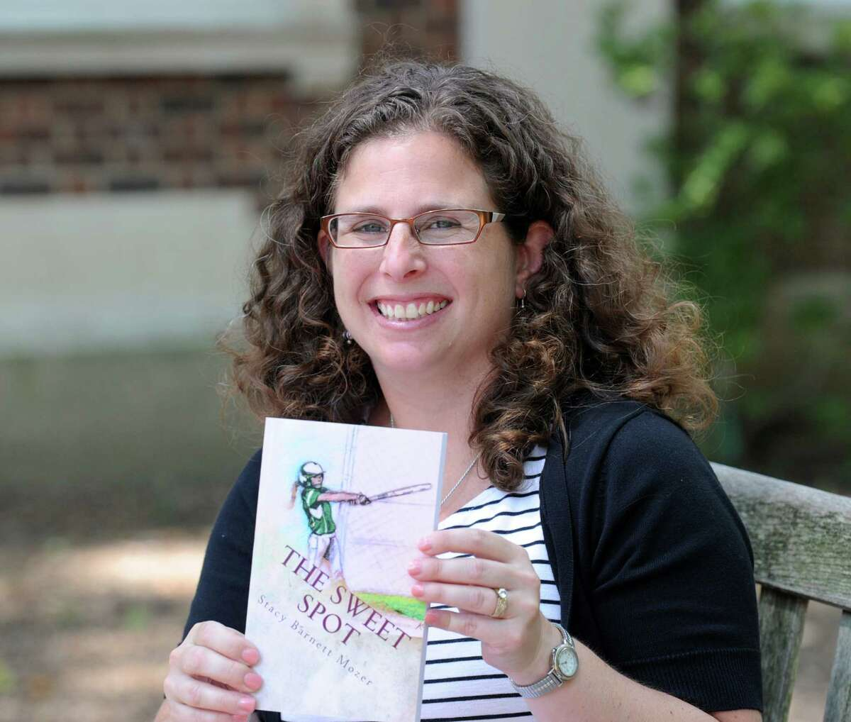 """Stacy Barnett Mozer, an author and Riverside School third-grade teacher, with her book """"The Sweet Spot,"""" at the school in the Riverside section of Greenwich."""
