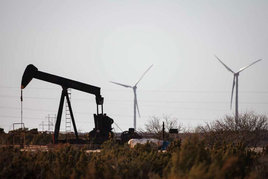 An oil well pumps oil as wind turbines produce energy in Fort Stockton.   ( Michael Paulsen / Houston Chronicle ) Photo: Michael Paulsen, Staff / Ã  2012 Houston Chronicle