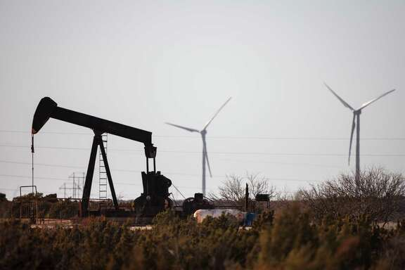 An oil well pumps oil as wind turbines produce energy in Fort Stockton.   ( Michael Paulsen / Houston Chronicle )