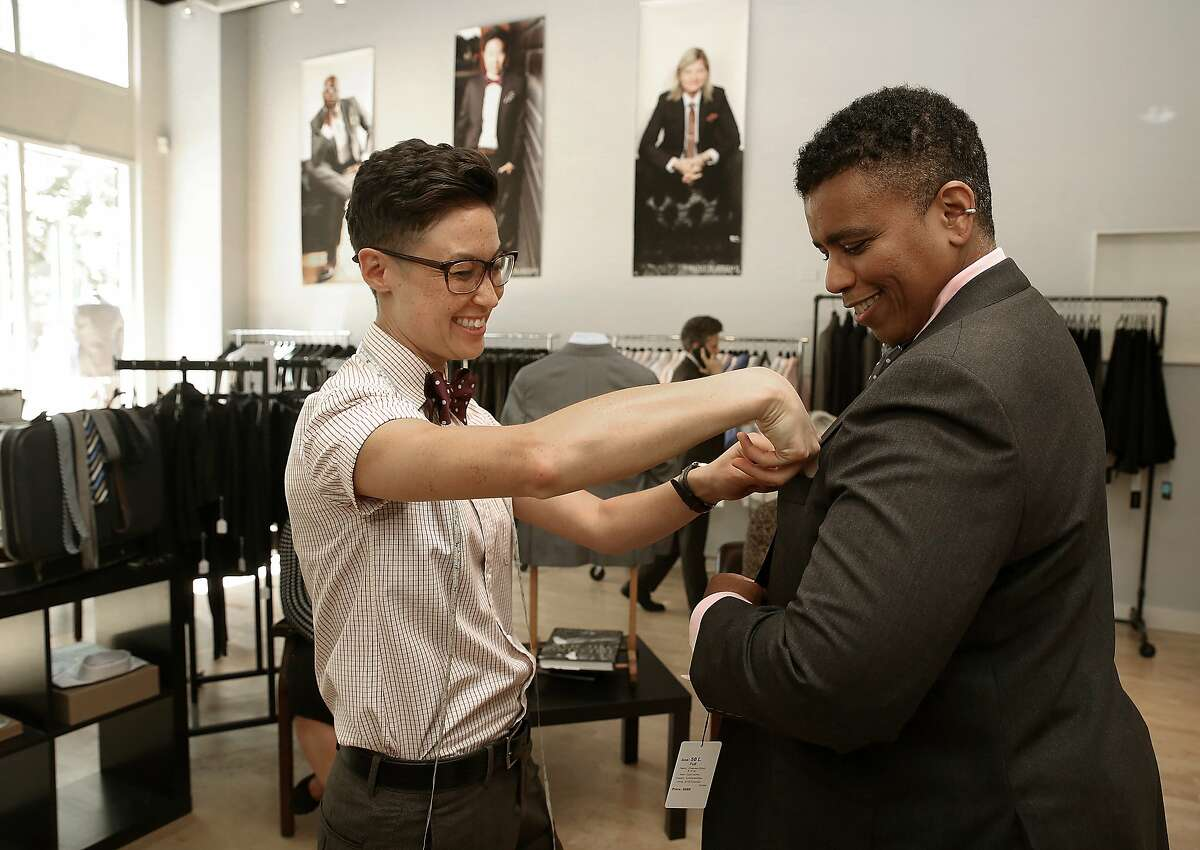 Mr. Dom Brassey (left) of Saint Harridan, a custom suit business for the LGBTQ community in Oakland, Calif., helps Dawn Robinson (right) try on a suit on Monday, August 3, 2015.