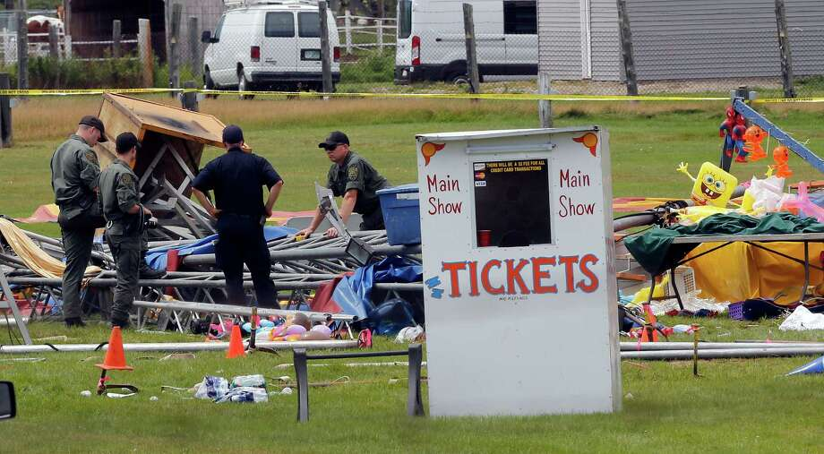 Investigators inspect the site where a circus tent collapsed Monday evening in Lancaster, N.H., during a storm with 60-mph winds, killing a man and his child. Photo: Jim Cole /Associated Press / AP