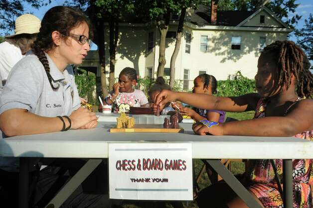 Albany PAL explorer Carimar Soto, left, plays chess with seven-year-old Zarryah Guinn during National Night Out in Pine Hills Park on Tuesday Aug. 4, 2015 in Albany, N.Y. (Michael P. Farrell/Times Union) Photo: Michael P. Farrell / 10032864A