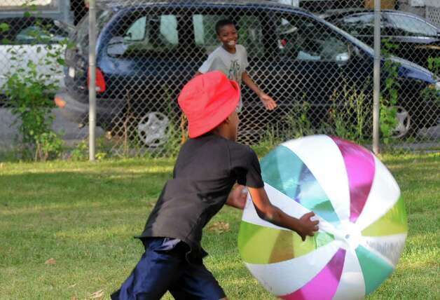 Ten-year-olds Poppa Hamlin, foreground, and Timmoure Miller play with a large beach ball during National Night Out in Pine Hills Park on Tuesday Aug. 4, 2015 in Albany, N.Y. (Michael P. Farrell/Times Union) Photo: Michael P. Farrell / 10032864A