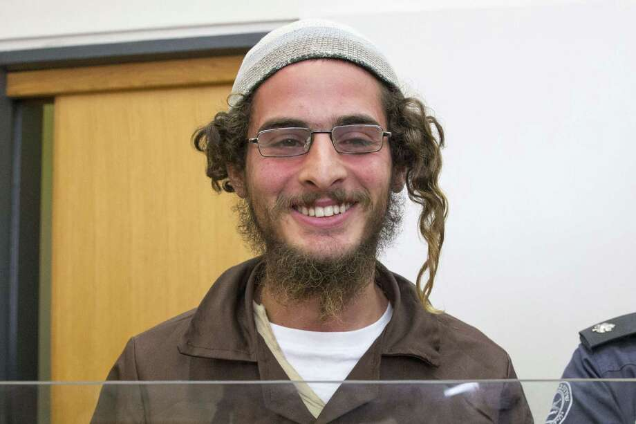 """Radical activist Meir Ettinger stands at the Israeli justice court in Nazareth Illit on Tuesday, a day after his arrest. Police said Ettinger was suspected of """"nationalist crimes"""" but did not accuse him of direct involvement in last week's firebombing in which a Palestinian toddler was burnt to death. Photo: JACK GUEZ, Staff / AFP"""