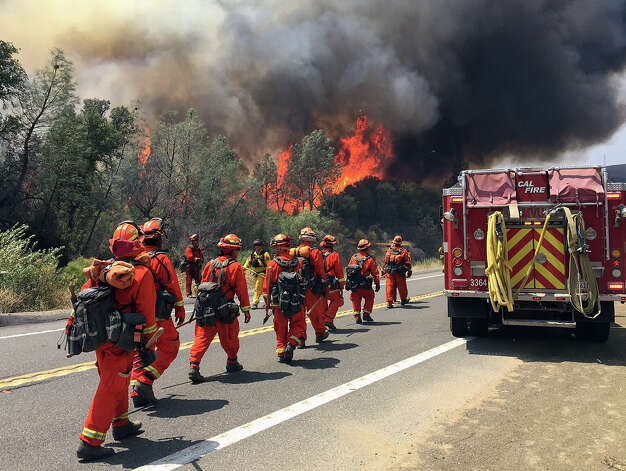 Fire crews walk on U.S. Highway 20 as a fire approaches near Clearlake, Calif., Monday, Aug. 3, 2015. Cooler weather helped crews build a buffer Monday between a raging Northern California wildfire and some of the thousands of homes it threatened as it tore through drought-withered brush that hadn't burned in years. (AP Photo/Terry Chea) ORG XMIT: FX101 Photo: Terry Chea / AP