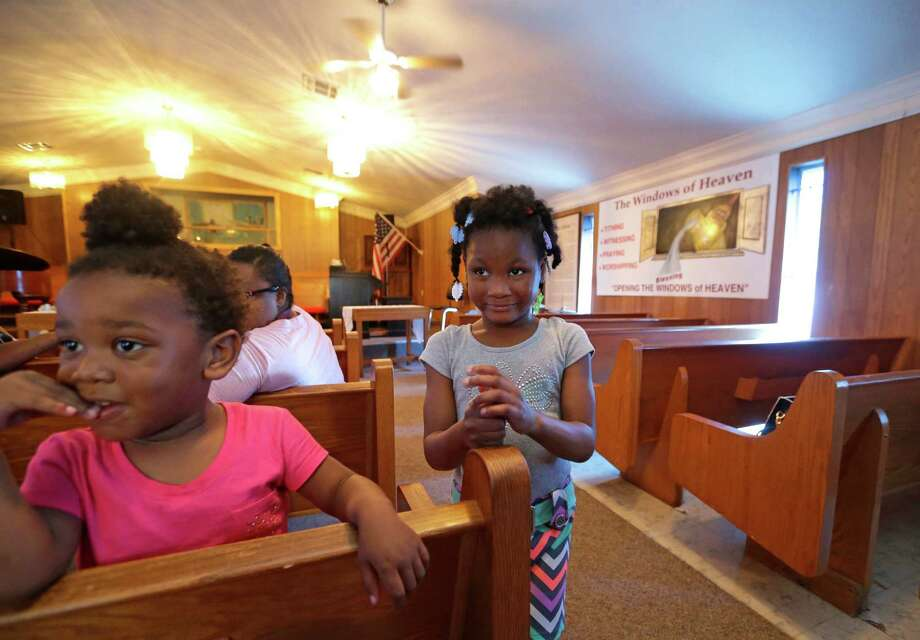 Chyna Gardley, 2, left, and Alazia Joseph, 6, play together at First Christian Fellowship Missionary Baptist Church on 3920 New Orleans St. after a news conference Tuesday to oppose the city's plan to buy the land. 