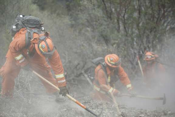 An inmate fire crew works on a fire line on the north side of Highway 20 near Clearlake, Calif., on Tuesday, Aug. 4, 2015. By creating fire lines, spreading of the Rocky Fire can be minimized. The inmate crew was made up of incarcerated individuals from Cal Fire's Ben Lomond Camp in Santa Cruz, Calif.