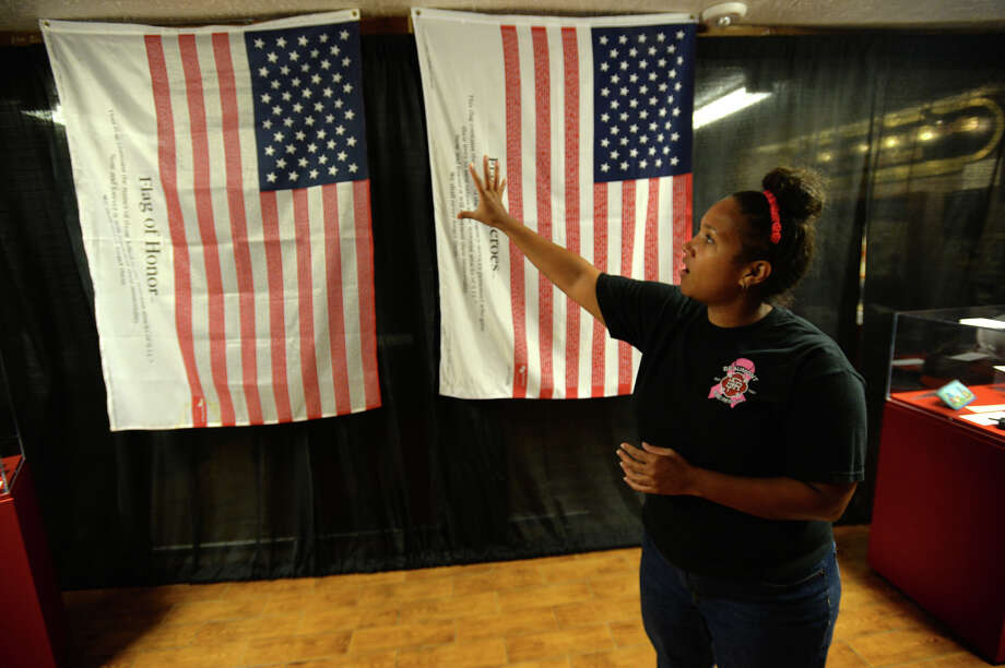 As part of the September 11, 2001: A Timeline exhibit, two American flags drawn by the names of 9/11 victims will be on display at the Beaumont Fire Museum from Wednesday to September 30. Ami Kamara stands by the flags that will be on view at the Beaumont Fire Museum from Wednesday to September 30.   Photo taken Tuesday, August 04, 2015  Guiseppe Barranco/The Enterprise Photo: Guiseppe Barranco, Photo Editor