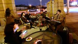 People listen to live music from Marjorie Grace Mathis outside the Mildred Building on Thursday night. Several establishments along Calder Avenue stayed open for Beaumont's First Thursday evening on the evening of February 5. Photo taken Thursday 2/5/15 Jake Daniels/The Enterprise