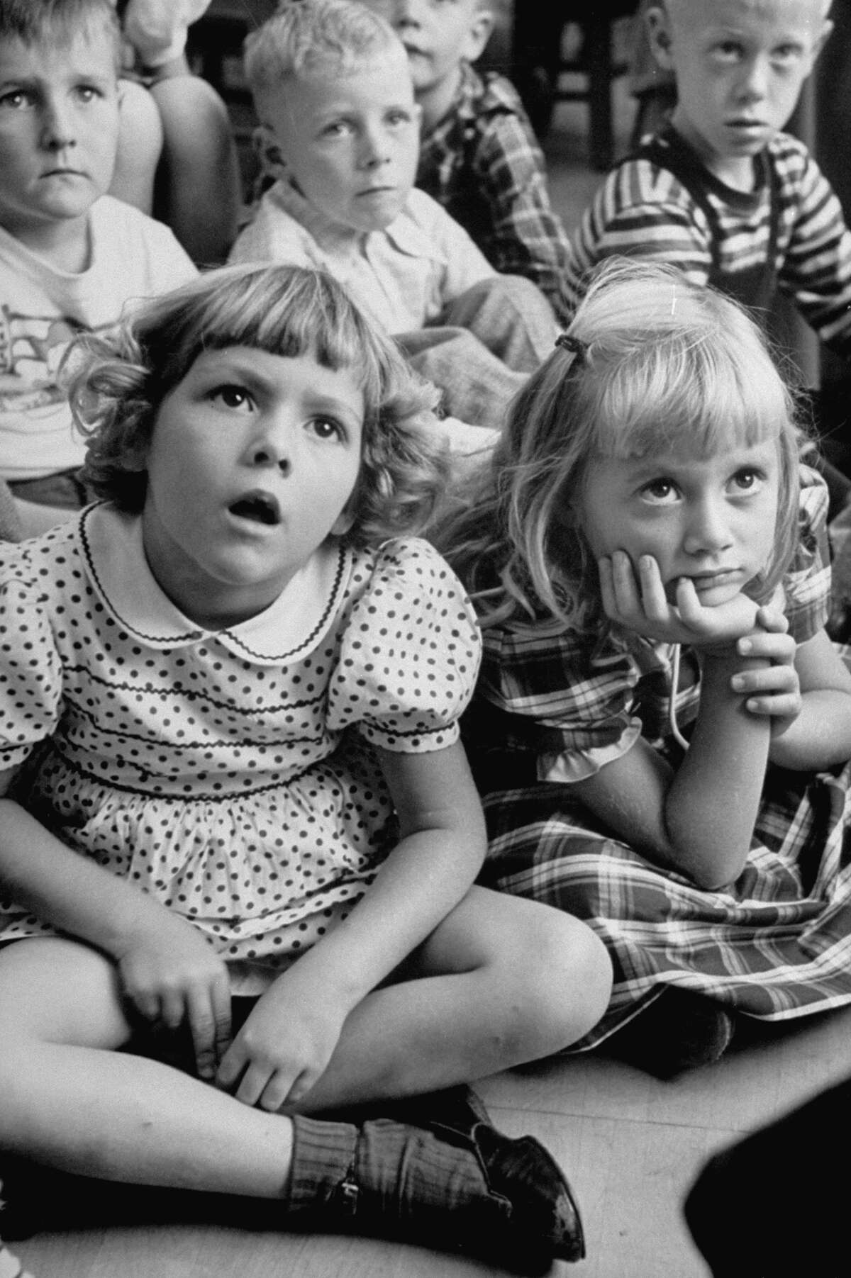 Wide-eyed children listening to fairy-tales on their first day at school.