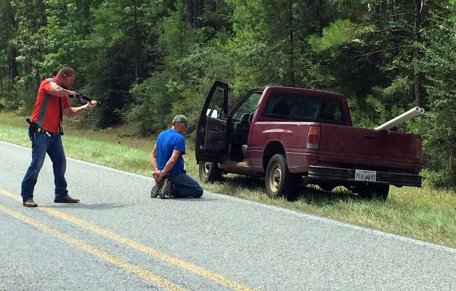 A Mississippi Bureau of Investigation agent detains a man for questioning after shots were fired for a second consecutive day near Camp Shelby, a military training center. Photo: Ryan Moore, Associated Press