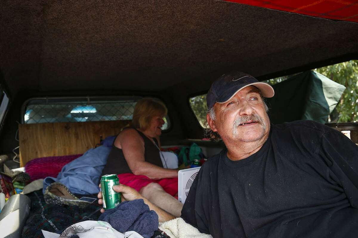 Mike Rousseau (front) and partner Suzi Carter pass the time in the back of their truck in front of the Moose Lodge near Clearlake, Calif., on Wednesday, Aug. 5, 2015. The pair was evacuated from the Double Eagle community last Saturday. They have been sleeping on a mattress in the back of their truck, anxiously awaiting clearance to return home.