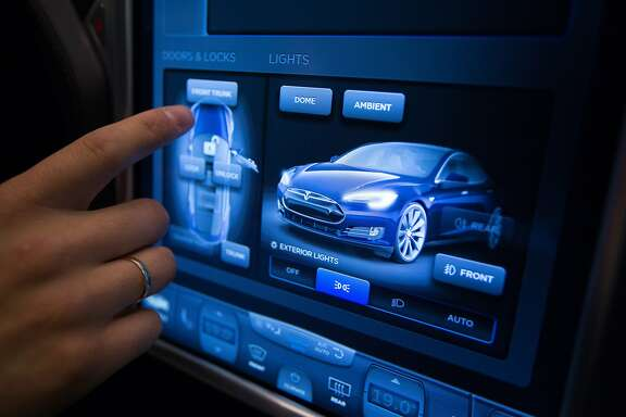 "A member of the Moscow Tesla Club demonstrates the operation of the touch-sensitive digital control screen inside a Tesla S P85D electric vehicle, manufactured by Tesla Motors Inc., on display at the Smolensky Passage shopping center in Moscow, Russia, on Sunday, July 13, 2015. Tesla said it doesn't sell its vehicles in Russia, so it doesn't ""provide warranty, charging solutions, service, or assistance with the necessary steps to legally import"" its cars. Photographer: Andrey Rudakov/Bloomberg"