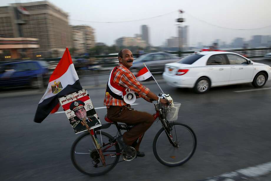A supporter of Egyptian President Abdel-Fattah el-Sissi carries his poster on his bike as he celebrates with others for Thursday's opening of the new extension of the Suez Canal, riding on the Qasr El Nile Bridge in Cairo. Photo: Hassan Ammar, Associated Press