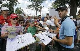 Dustin Johnson sign autographs during the practice round of the Bridgestone Invitational golf tournament at Firestone Country Club, Wednesday, Aug. 5, 2015, in Akron, Ohio. (AP Photo/Tony Dejak)