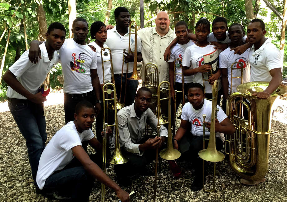 Sacred Heart University's Director of Bands Keith Johnston, standing at center, with the low brass section of the Holy Trinity School of Music Summer Music Camp in Haiti.  Sacred Heart University Director of Bands Keith Johnston, standing at center, with the low brass section of the Holy Trinity School of Music Summer Music Camp in Haiti. Photo: Contributed / Contributed / Connecticut Post