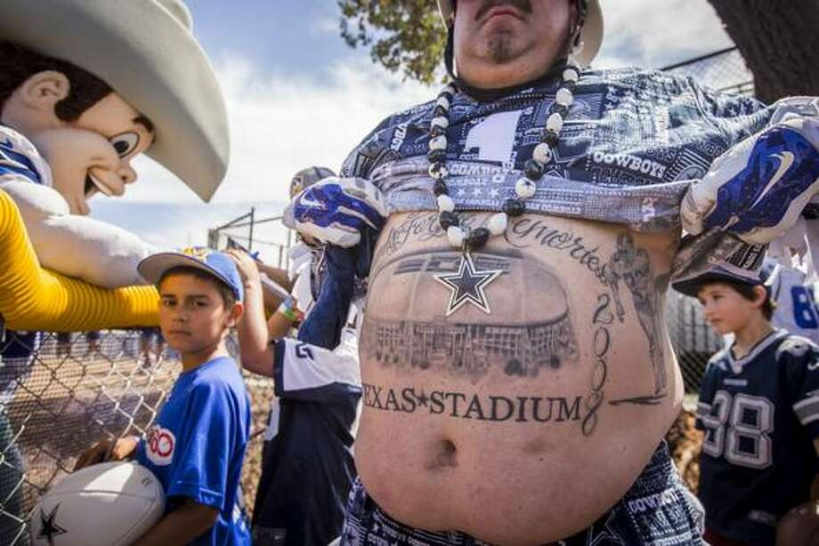 "Dallas Cowboys fan ""Tattoo Mark"" Shenefield shows off one of his tattoos, a memorial to Texas Stadium, while waiting for his team to take the field for practice at training camp on Sunday, Aug. 2, 2015, in Oxnard, Calif. (Smiley N. Pool/The Dallas Morning News)"