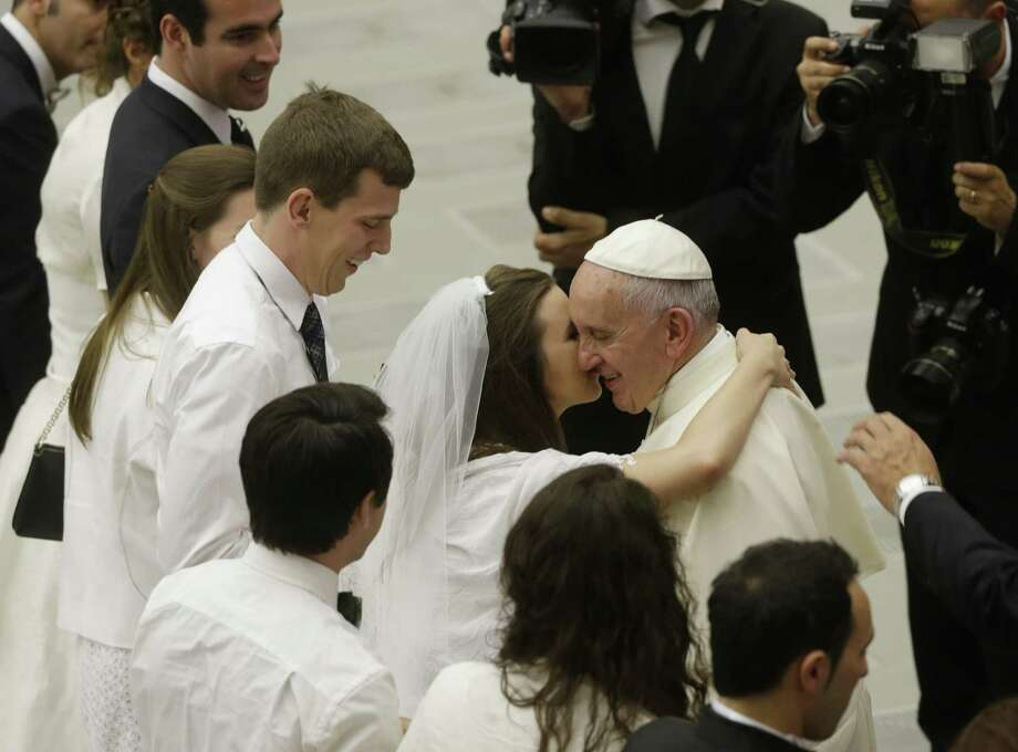 Pope Francis greets newlyweds during the general audience in the Paul VI hall at the Vatican, Wednesday, Aug. 5, 2015. Pope Francis says divorced Catholics who remarry and their children deserve better treatment from the Catholic church. (AP Photo/Gregorio Borgia) Photo: Gregorio Borgia, STF / AP