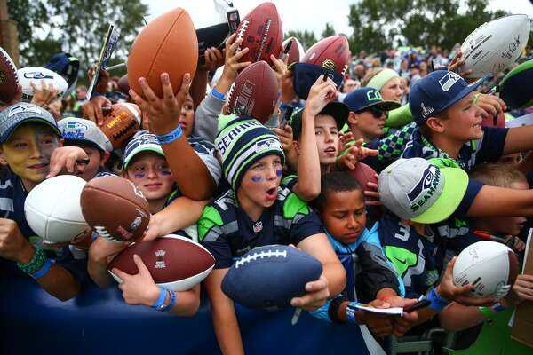 Fans scramble for autographs during Seahawks training camp. Photographed on Wednesday, August 5, 2015 at the Virgina Mason Athletic Facility in Renton. (Joshua Trujillo, seattlepi.com)