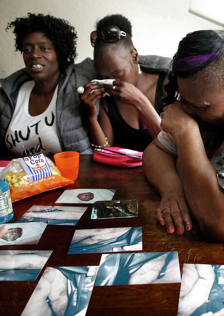 Yvonne Fletcher (left), Tasha Dillard and Effie Haynes become tearful as they look at pictures of the battered body of their relative Alvin Haynes. Photo: Liz Hafalia / Liz Hafalia / The Chronicle / ONLINE_YES