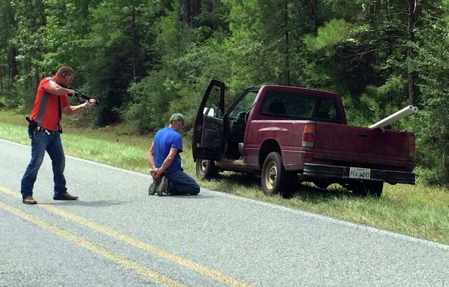 A Mississippi Bureau of Investigation agent detains Alfred Baria on Wednesday after loud noises first thought to be gunshots fired for consecutive days near Camp Shelby, a military training site near Hattiesburg, Miss. Photo: Ryan Moore, TEL / WDAM-TV