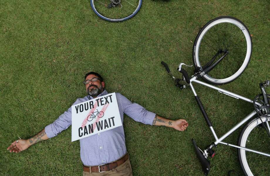 Robert Rios sets down his bicycle in a silent protest for 4 minutes outside City Hall to remind motorist to share the road with cyclists on Tuesday, June 23, 2015, in Houston. ( Mayra Beltran / Houston Chronicle ) Photo: Mayra Beltran, Staff / © 2015 Houston Chronicle