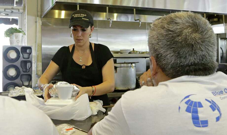 Dayamyra Perez Fernandez prepares a lunch to go for a customer at a local grocery store in the Little Havana area of Miami. The Institute for Supply Management said its services index rose to 60.3 last month, the highest since the index was created in 2008 and up from 56 in June. Photo: Alan Diaz /Associated Press / AP