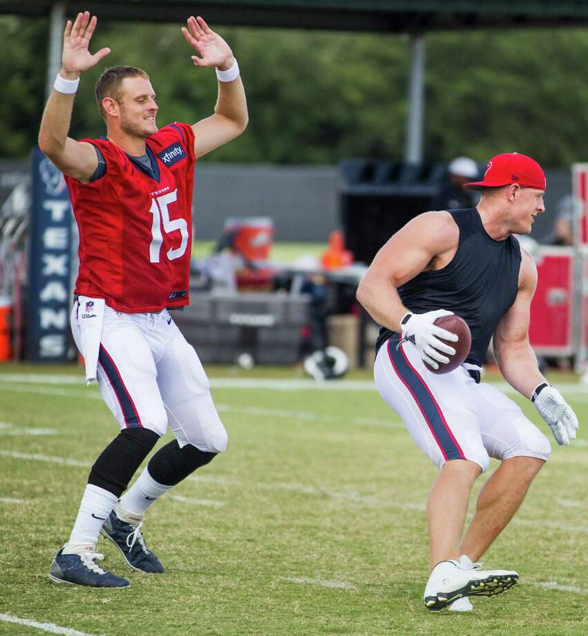 In a bit of post-practice role reversal, Ryan Mallett, left, gives chase as a defender while J.J. Watt takes a turn as quarterback Wednesday. Photo: Brett Coomer, Staff / © 2015 Houston Chronicle