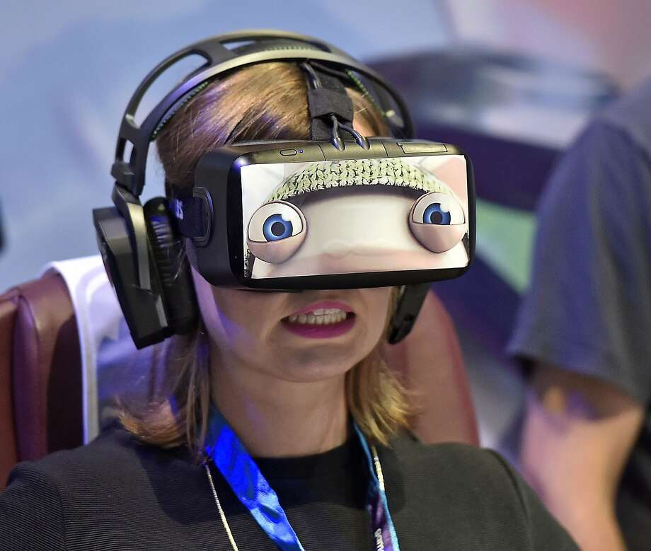 A woman wears a virtual reality  head-mounted display  at the gamescom fair in Cologne, Germany, Wednesday, Aug. 5, 2015.  Hundreds of thousands of  visitors  will  enjoy one of the world's largest computer and video game events  until Sunday.  Photo: Martin Meissner, Associated Press