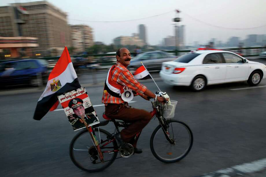 A backer of Egyptian President Abdel-Fattah el-Sissi marks the opening of the new Suez Canal extension while riding on the Qasr El Nile Bridge in Cairo. Photo: Hassan Ammar, STF / AP