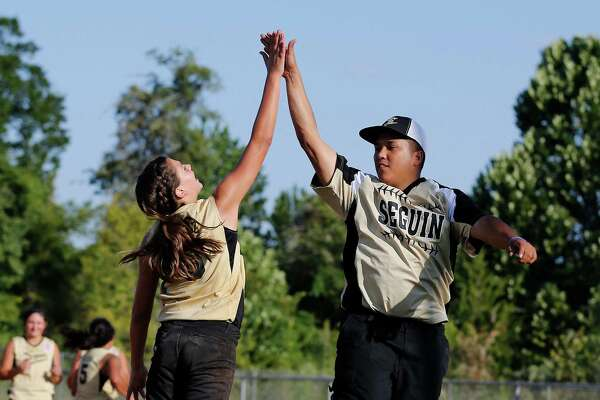 Coach Kiet Le (right) gives a high-five to Seguin Majors' Haileigh Ortiz (06) after the softball team defeated Greater Helotes in the championship game of the 2015 Little League Softball Southwest Region Tournament in Waco on Wednesday, Aug. 5, 2015. Seguin held off Helotes to win, 6-4, and move on to play in the World Series tournament in Portland, Oregon.