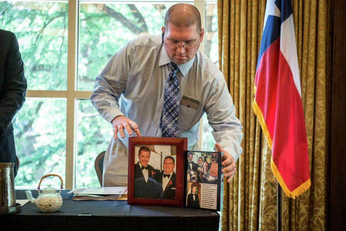 John Stone-Hoskins arranges photos of his late husband, James, at a news conference Wednesday.