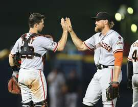 San Francisco Giants catcher Buster Posey, left, and San Francisco Giants right fielder Hunter Pence celebrate after defeating the Atlanta Braves 6-1in a baseball game, Wednesday, Aug. 5, 2015, in Atlanta. (AP Photo/John Bazemore)