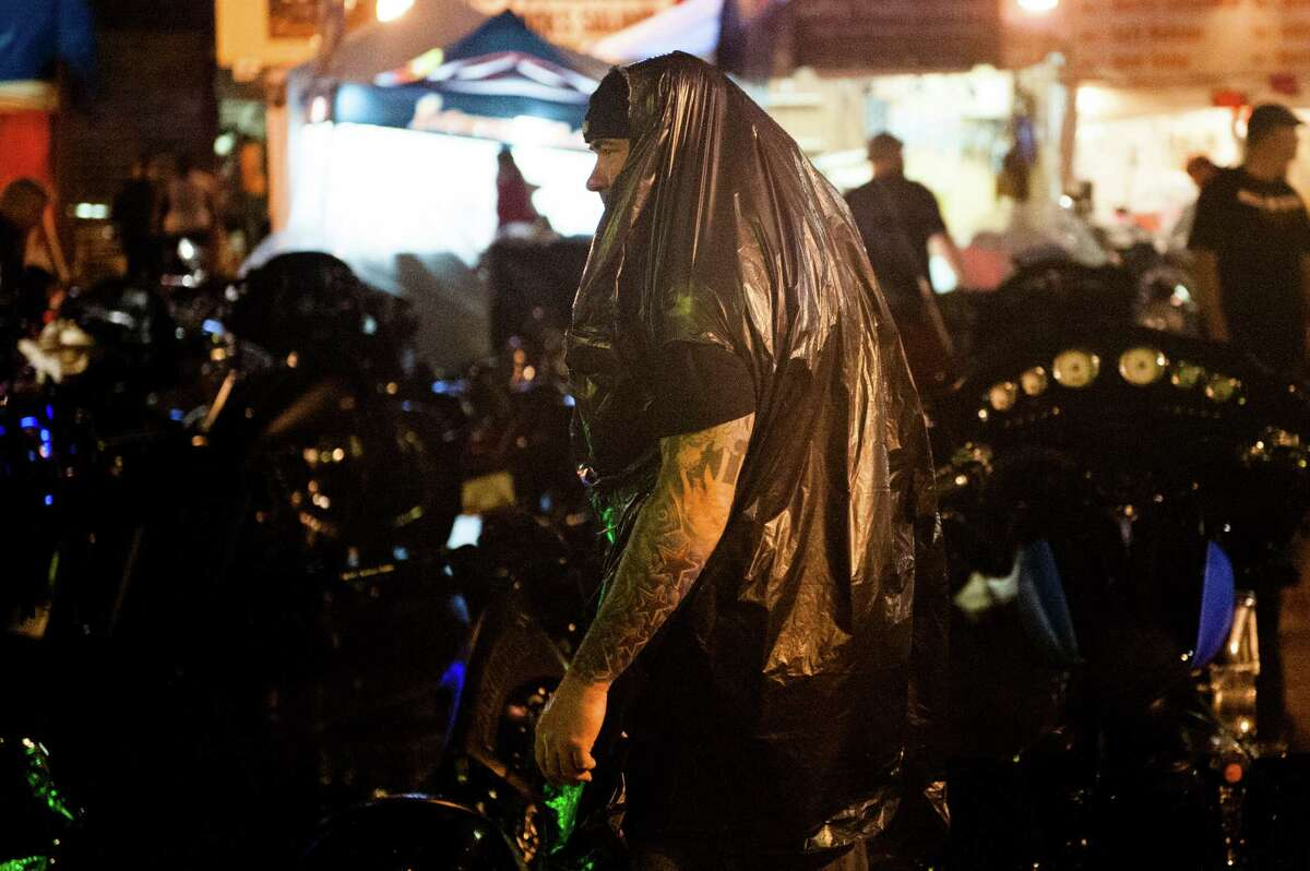 STURGIS, SD - AUGUST 3: A biker wears a garbage bag to avoid the rain during a late-night thunderstorm on the first day of the annual Sturgis Motorcycle Rally August 3, 2015 in Sturgis, South Dakota. This year marks the 75th anniversary of the rally, with crowds of up to 1.2 million people expected to visit.