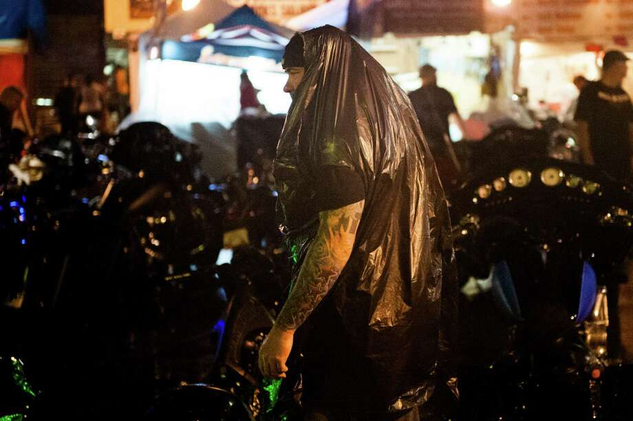 STURGIS, SD - AUGUST 3: A biker wears a garbage bag to avoid the rain during a late-night thunderstorm on the first day of the annual Sturgis Motorcycle Rally August 3, 2015 in Sturgis, South Dakota. This year marks the 75th anniversary of the rally, with crowds of up to 1.2 million people expected to visit. Photo: Andrew Cullen, Getty Images / 2015  Getty Images