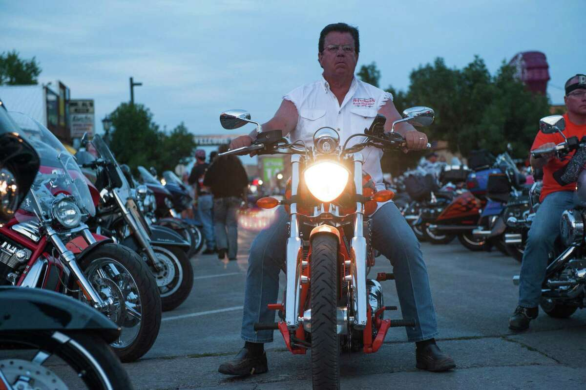 STURGIS, SD - AUGUST 3: A biker rides downtown on the first day of the annual Sturgis Motorcycle Rally August 3, 2015 in Sturgis, South Dakota. This year marks the 75th anniversary of the rally, with crowds of up to 1.2 million people expected to visit.