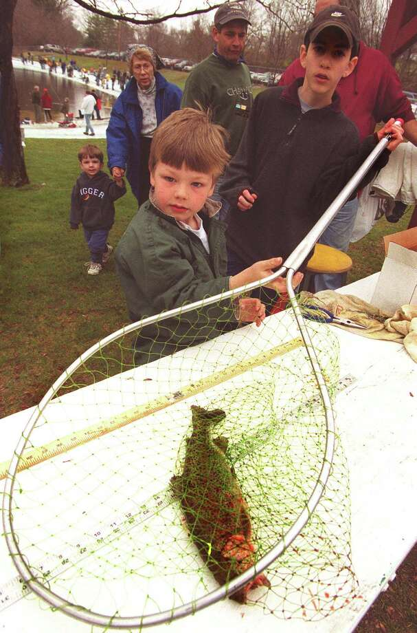 "12 yr ols Mike Schirmer of N.F., right, measures a 15 "" Rainbow trout that 5 yr old John Borchert of Newtown, left caught in the Fishing Derby. Photo: Michael Duffy\file Photo / Michael Duffy\file Photo / The News-Times File Photo"