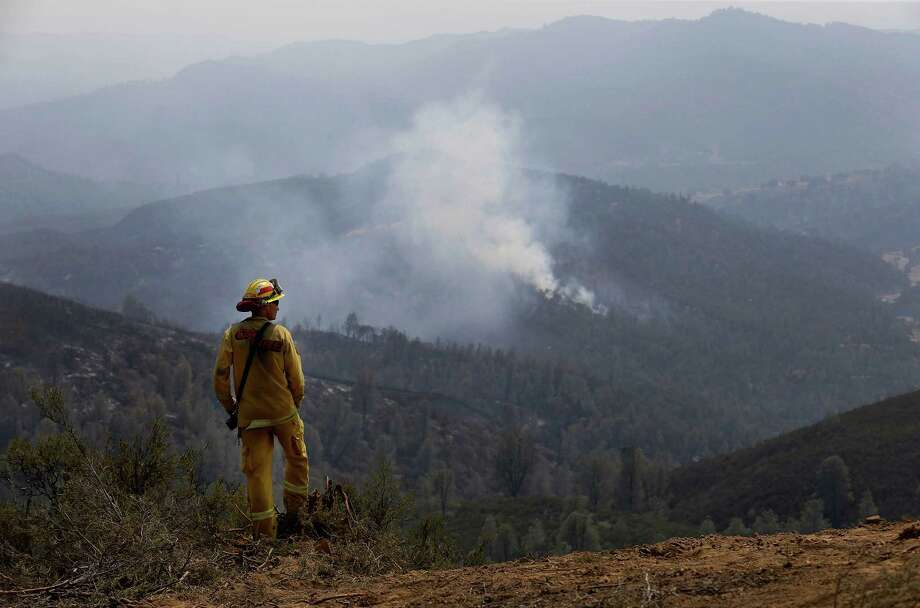 Cal Fire engineer Clint Singleton looks out at a plume of smoke near Clearlake, Calif., Wednesday, Aug. 5, 2015. Thousands of firefighters battling an unruly Northern California wildfire were aided overnight by cooler temperatures and higher humidity, but the fire is still less than a quarter contained. Photo: Jeff Chiu, AP / AP