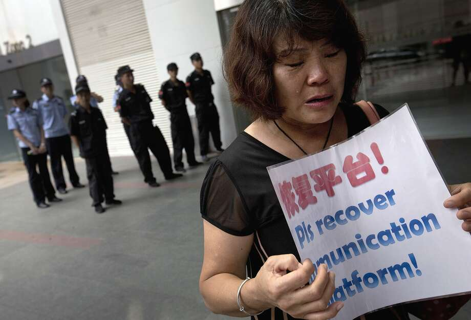 A relative of a Flight MH370 passenger weeps outside the Malaysia Airlines office in Beijing. Photo: Andy Wong, Associated Press