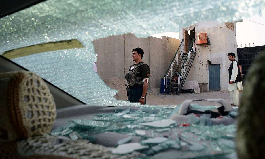 Afghan security personnel are seen through the shattered window of a vehicle as they stand alert at the scene of a Taliban attack that killed two police officers in the city of Kandahar. Photo: Jawed Tanveer, AFP / Getty Images