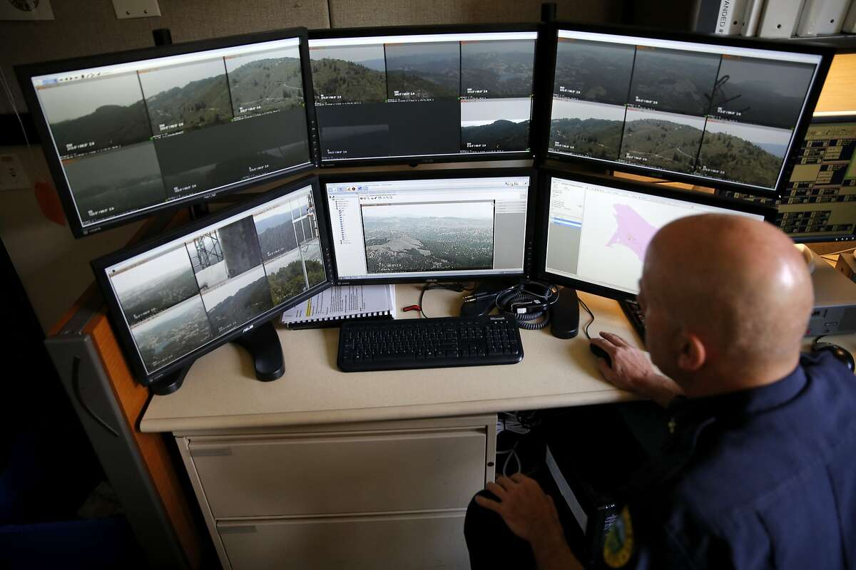 Battalion chief Michael Giannini pulls up different feeds on the screens that show live photos from cameras looking for wildfires while at Marin County Fire Department headquarters in Woodacre, California, on Thursday, Aug. 6, 2015.