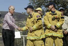 Gov. Jerry Brown, left, shakes hands with Sacramento Metro firefighter Josh Larson at a news conference at Cowboy Camp Trailhead near Clearlake, Calif., Thursday, Aug. 6, 2015. Crews backed by important firefighting resources are gaining ground against a massive Northern California wildfire, but it may be several days before thousands of evacuees can return home, officials said Thursday. (AP Photo/Jeff Chiu)
