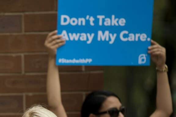 An opponent and supporter of Planned Parenthood demonstrate Tuesday, July 28, 2015, in Philadelphia. Anti-abortion activists are calling for an end to government funding for the nonprofit reproductive services organization. (AP Photo/Matt Rourke)