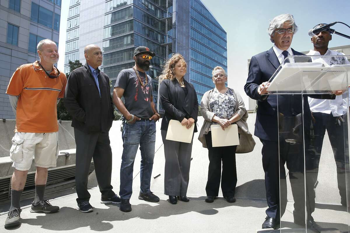 Uber counsel Ted Boutrous (at podium) holds a press conference at the plaza entrance of 450 Golden Gate Ave. in San Francisco, Calif., on Thursday, August 6, 2015. Boutrous and some Uber drivers (behind) discuss the O'Conner vs. Uber lawsuit seeking to reclassify Uber drivers in California as employees.